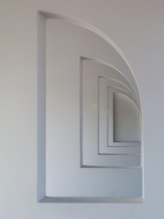 As aberturas semi arqueadas no estuque branco terminaram paredes na perspectiva de diminuição fotos de stock