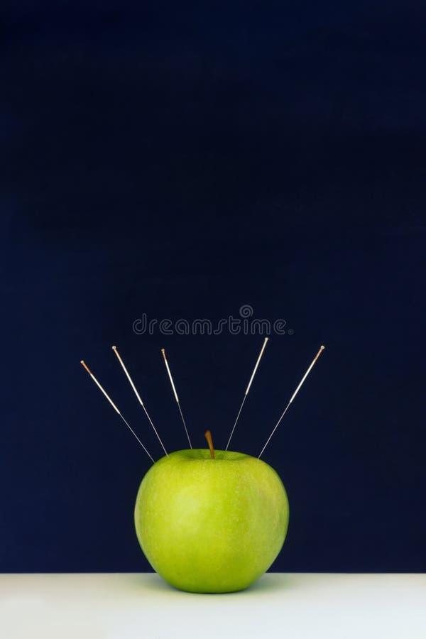 As agulhas da acupuntura colaram em uma maçã verde como um símbolo fotos de stock royalty free