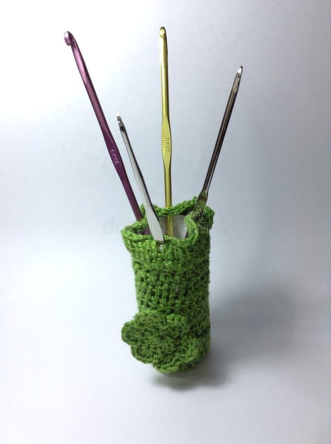 As agulhas de crochê no verde fazem crochê o suporte fotos de stock