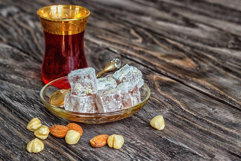 As alegrias turcas com porcas diferentes são um vidro do chá e de uma colher Doces orientais Lokum tradicional de Rahat do loukou fotografia de stock royalty free