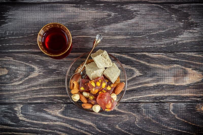 As alegrias turcas com porcas diferentes são um vidro do chá e de uma colher Doces orientais Lokum tradicional de Rahat do loukou fotos de stock