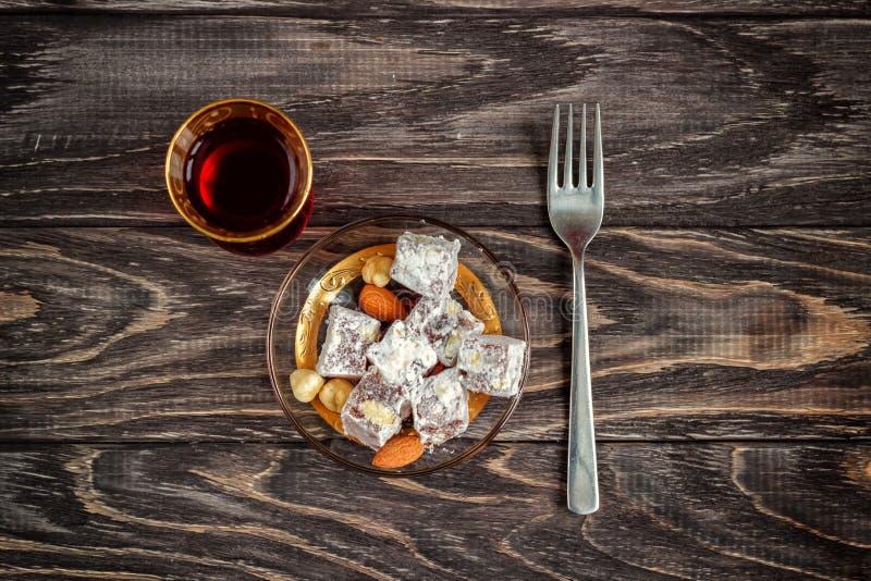 As alegrias turcas com porcas diferentes são um vidro do chá e de uma colher Doces orientais Lokum tradicional de Rahat do loukou fotos de stock royalty free