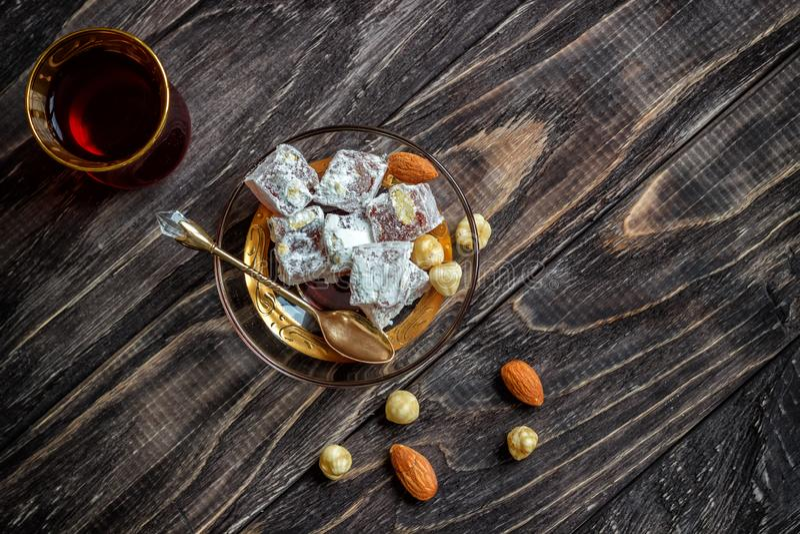As alegrias turcas com porcas diferentes são um vidro do chá e de uma colher Doces orientais Lokum tradicional de Rahat do loukou fotografia de stock