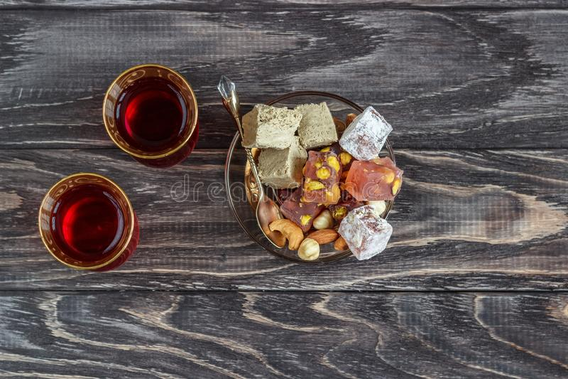 As alegrias turcas com porcas diferentes são um vidro do chá e de uma colher Doces orientais Lokum tradicional de Rahat do loukou imagens de stock royalty free