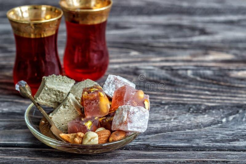 As alegrias turcas com porcas diferentes são um vidro do chá e uma colher Doces orientais Lokum tradicional de Rahat do loukoum n foto de stock royalty free