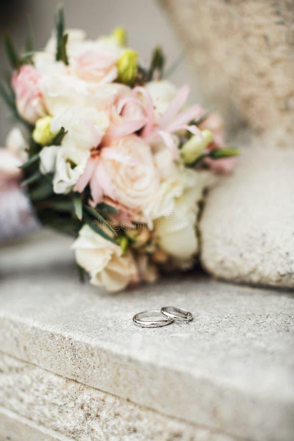 As alianças de casamento bonitas encontram-se em uma superfície de madeira contra a parte traseira fotos de stock