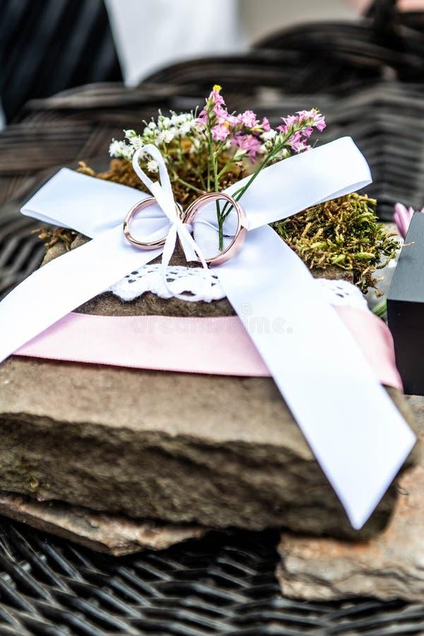 As alianças de casamento bonitas encontram-se na superfície da pedra na perspectiva de um ramalhete de pares do casamento das flo fotos de stock