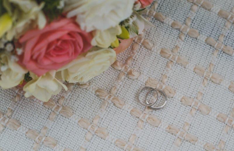 As alianças de casamento do ouro branco encontram-se em um tapete bege, um ramalhete nupcial foto de stock royalty free