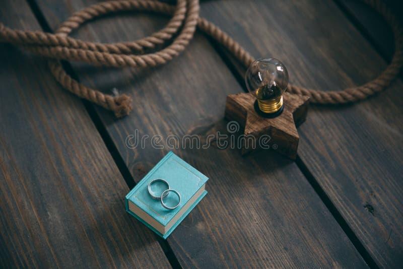 As alianças de casamento do ouro encontram-se em uma caixa de presente azul em uma tabela retro de madeira marrom Decoração com l fotografia de stock royalty free