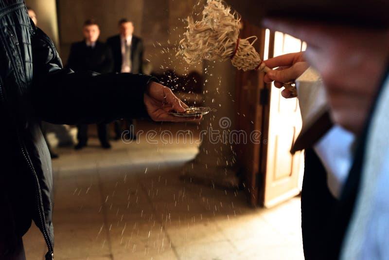 As alianças de casamento douradas na placa na mão do padre em tradicional cere foto de stock royalty free