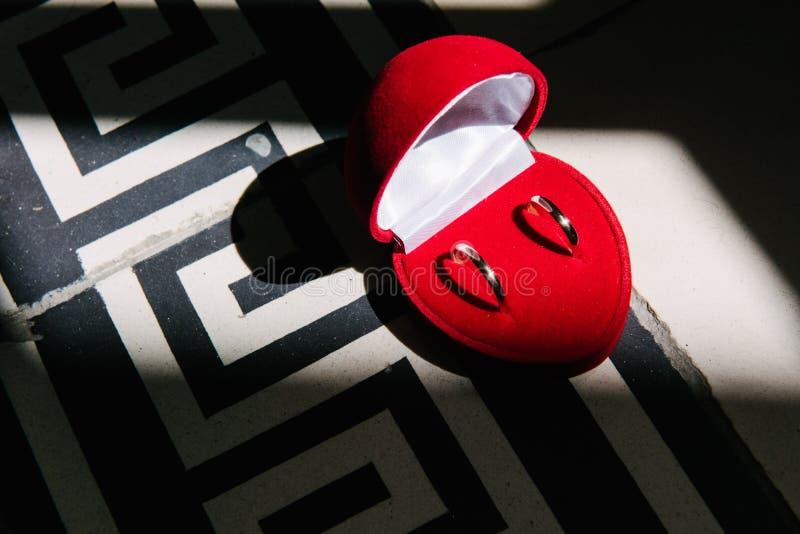 As alianças de casamento encontram-se em uma caixa coração-dada forma vermelha fotos de stock