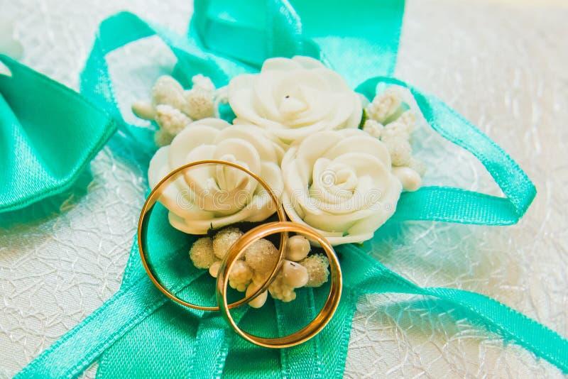 As alianças de casamento estão em um descanso branco e sadely no ramalhete da noiva imagens de stock
