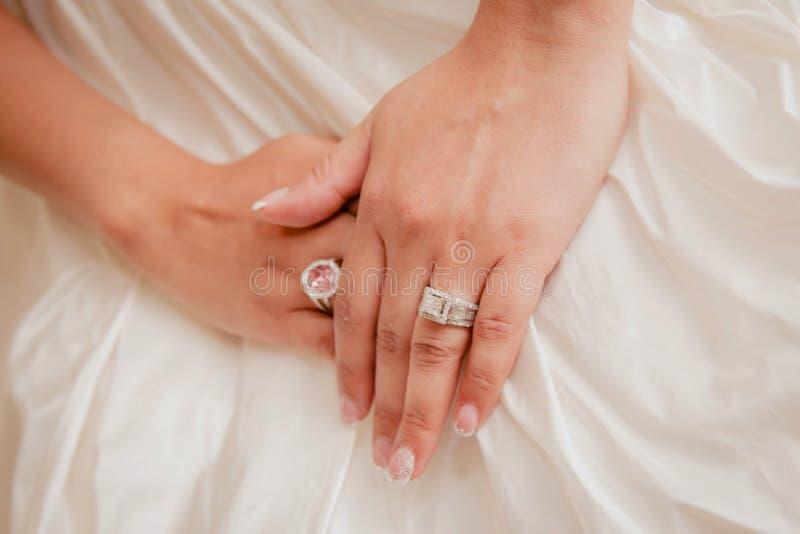As alianças de casamento nupciais bonitas projetam Decorado com um toque do projeto bonito branco do vestido de casamento fotos de stock