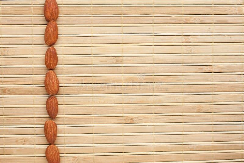 Amêndoas descascadas que encontram-se em uma esteira de bambu fotografia de stock