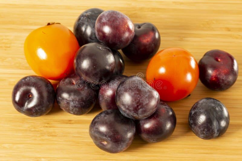 As ameixas vermelhas e os frutos alaranjados do caqui fecham-se acima da vista isolados no fundo de madeira Frutifica o conceito  fotografia de stock