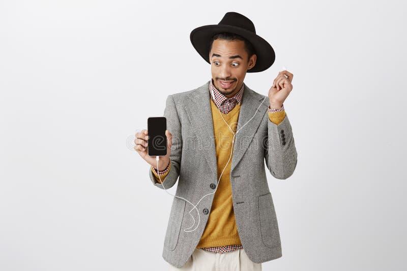 As amigas de Tok telefonam para escutar música, chocada de seu gosto Moderno africano bonito embaraçado confuso dentro fotografia de stock