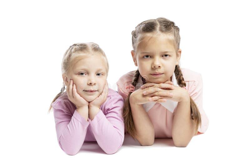 As amigas em camisetas cor-de-rosa estão encontrando-se e estão sorrindo-se Crian?as pequenas Isolado sobre o fundo branco imagens de stock royalty free