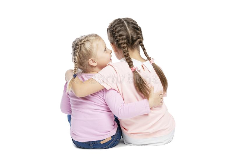 As amigas em camisetas e em calças de brim cor-de-rosa estão abraçando e estão rindo Vista traseira Isolado sobre o fundo branco fotos de stock royalty free