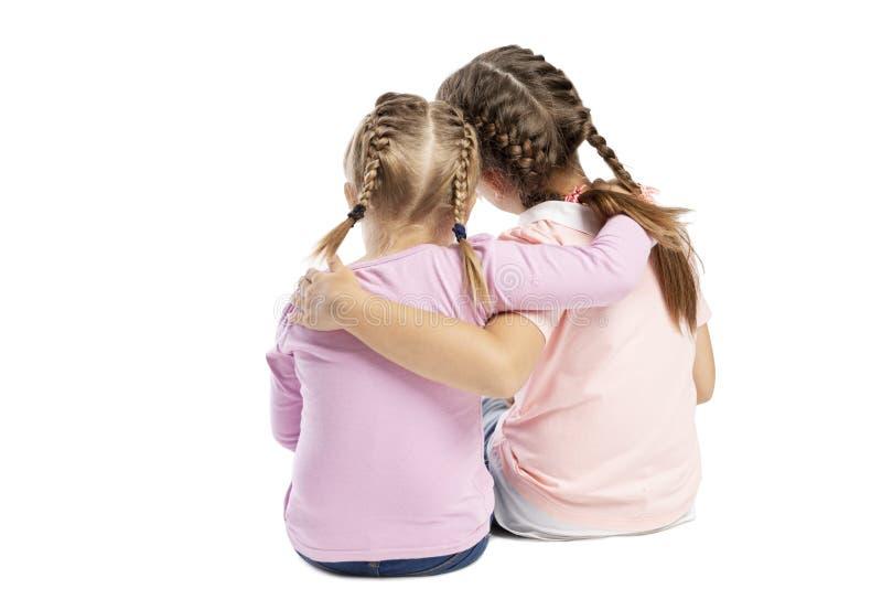 As amigas em camisetas e em calças de brim cor-de-rosa estão abraçando Vista traseira Isolado sobre o fundo branco fotografia de stock