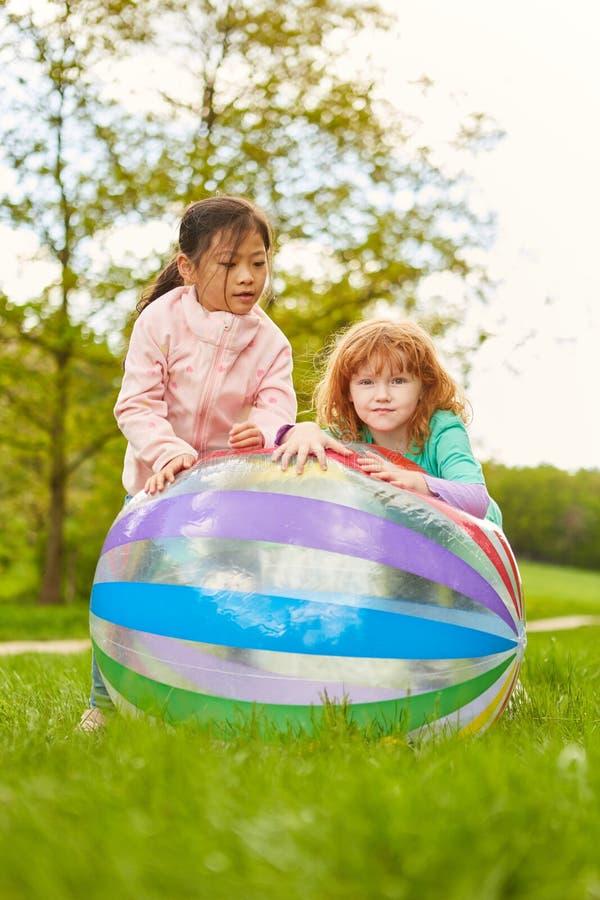 As amigas jogam junto com uma bola imagem de stock