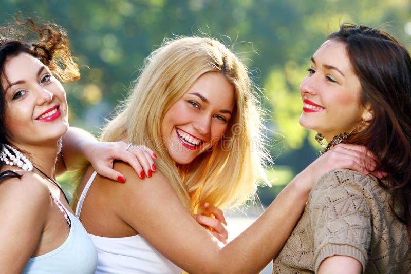 As amigas novas e bonitas têm o divertimento no parque foto de stock royalty free