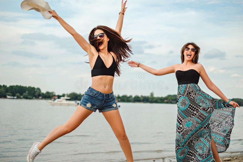 As amigas que saltam na praia foto de stock