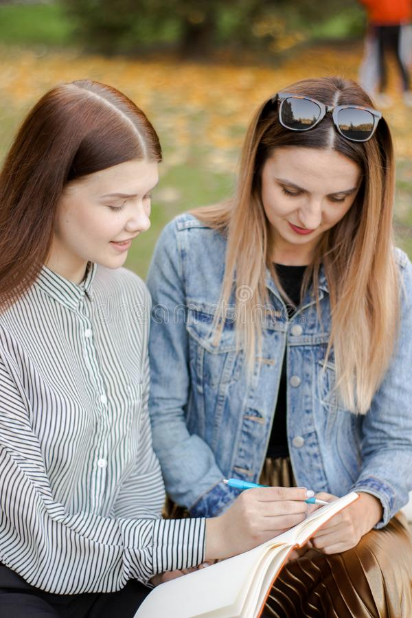 As amigas tomam notas ao sentar-se em um banco no parque do outono fotografia de stock