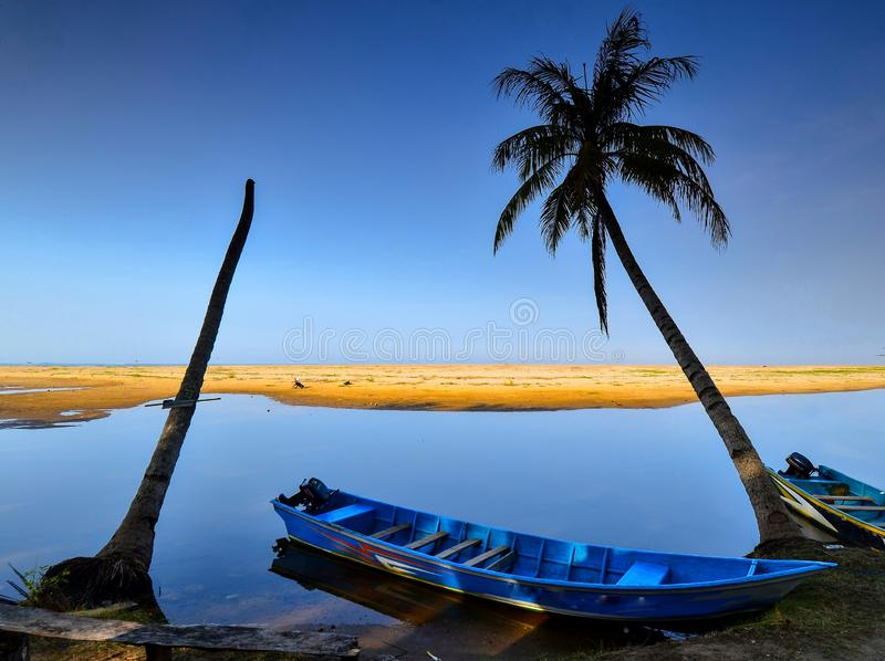 As areias e o laguna brancos com uma palmeira e o barco foto de stock royalty free
