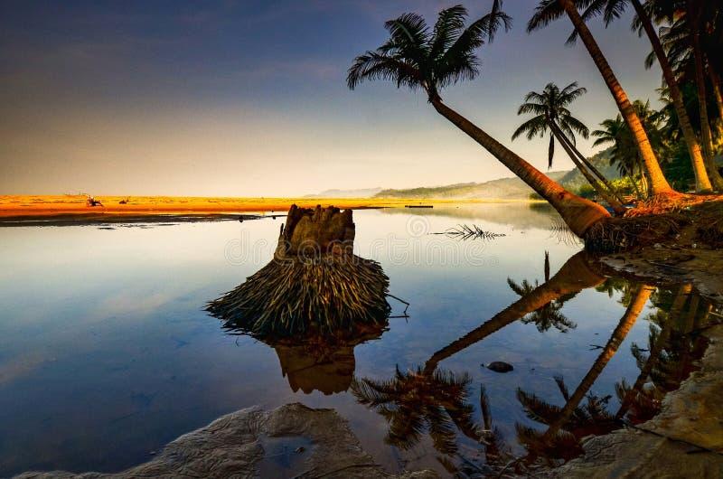As areias e o laguna brancos com uma palmeira e o barco imagens de stock royalty free