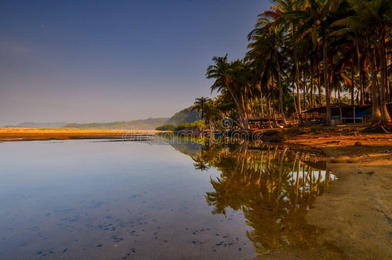 As areias e o laguna brancos com uma palmeira e o barco imagem de stock royalty free