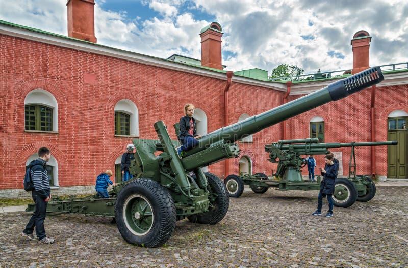 As armas da segunda guerra mundial nas paredes da fortaleza e das crianças que jogam em torno delas foto de stock royalty free