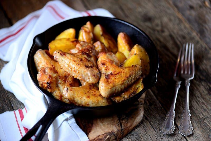 As asas de galinha cozeram com as batatas nas especiarias e nas ervas aromáticas - manjericão, alecrins, aneto e alho na frigidei fotos de stock royalty free