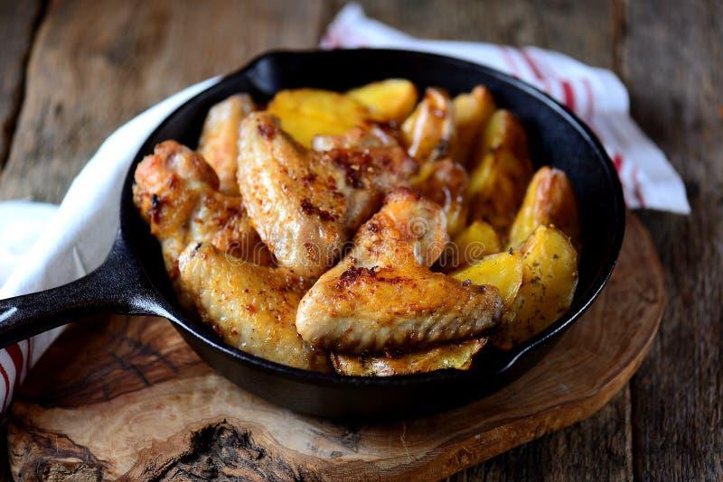 As asas de galinha cozeram com as batatas nas especiarias e nas ervas aromáticas - manjericão, alecrins, aneto e alho na frigidei foto de stock