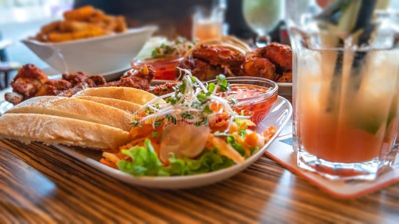 As asas de galinha grelhadas, batatas ocidentais cozidas, chinês doce salmouram e salada fresca no restaurante exterior imagens de stock