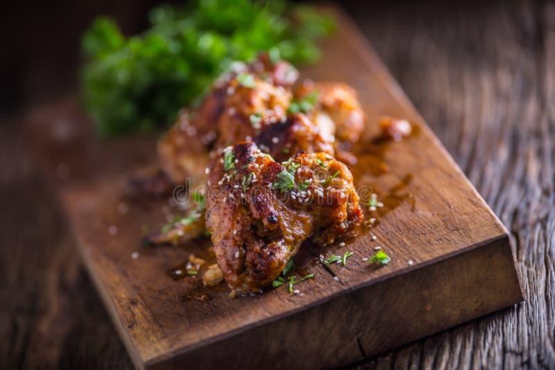 As asas de galinha grelharam a erva e o sésamo da salsa do BBQ na placa de madeira imagem de stock royalty free