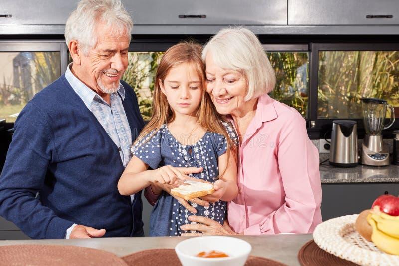 As avós ajudam o pão da mancha da neta foto de stock royalty free