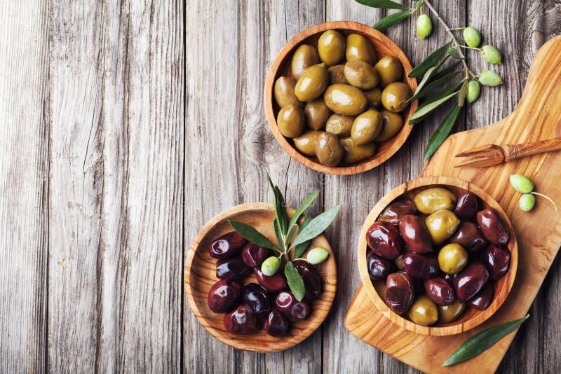 As azeitonas conservadas serviram em umas bacias da madeira verde-oliva na opinião superior rústica de mesa de cozinha foto de stock royalty free