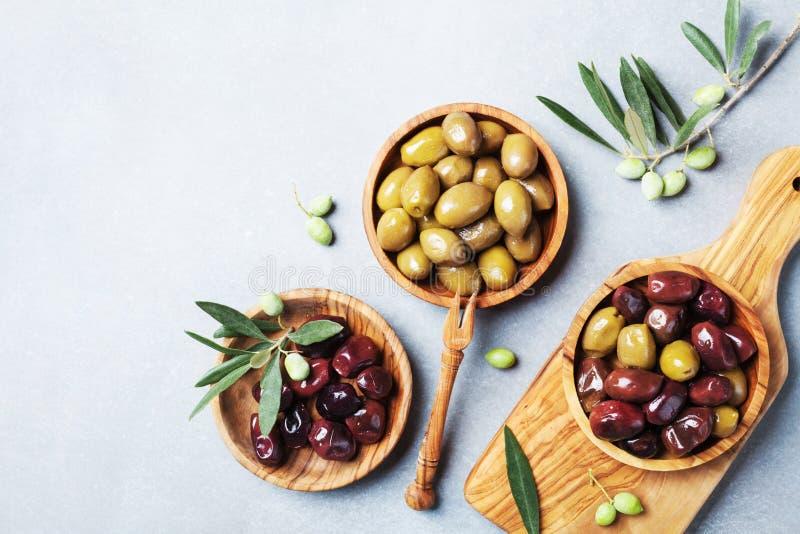 As azeitonas conservadas serviram em umas bacias da vista superior de madeira verde-oliva imagem de stock