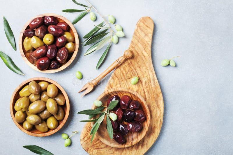 As azeitonas gregas naturais em umas bacias com cozinha embarcam da opinião superior da oliveira foto de stock royalty free