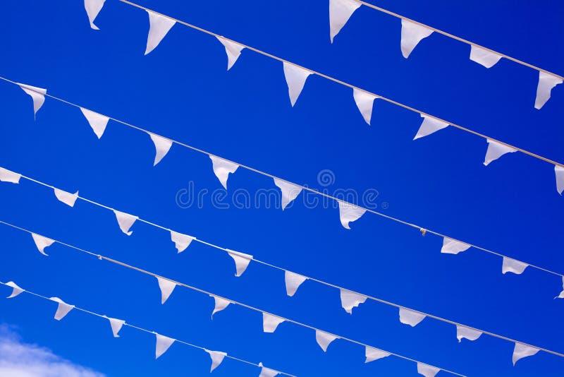 As bandeiras brancas que acenam no vento, fim do fundo do céu azul acima, bandeiras batem na brisa, flutuadores decorativos das f imagem de stock royalty free