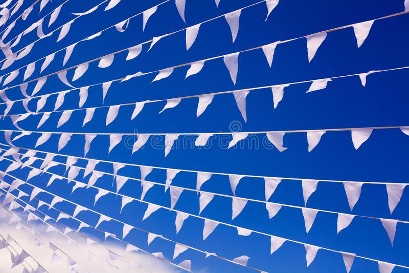 As bandeiras brancas que acenam no vento, fim do fundo do céu de azuis marinhos acima, bandeiras batem na brisa, flutuadores deco fotografia de stock