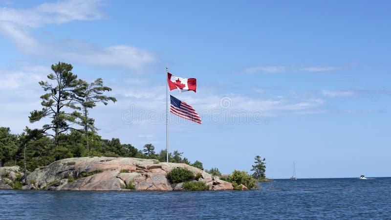 As bandeiras canadenses e americanas cumprimentam barqueiros como incorporam o canal de Killarney na baía Georgian, Ontário imagem de stock royalty free