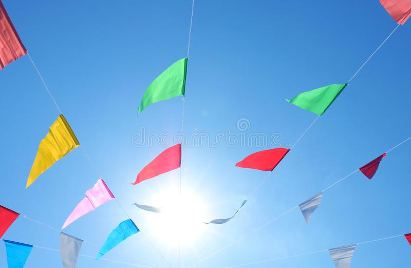 As bandeiras coloridas no fundo do céu e da luz solar, bandeiras alinham a linha de bandeira e o céu extravagantes, coloridos do  imagem de stock