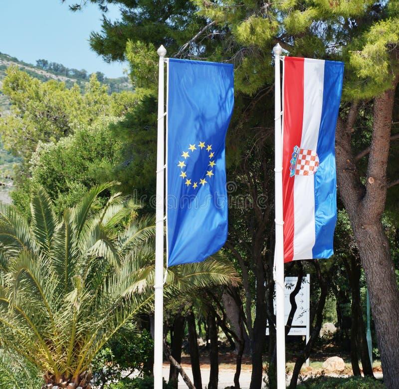 As bandeiras croatas e europeias que flutuam de lado a lado imagens de stock