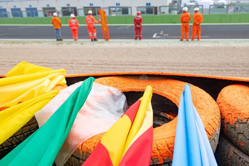 As bandeiras de advertência do esporte automóvel fecham-se acima na barreira do circuito de competência foto de stock royalty free
