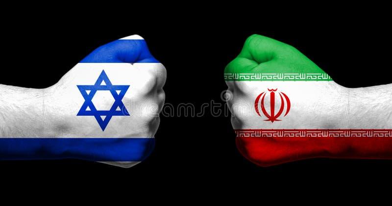 As bandeiras de Israel e de Irã pintados em dois apertaram os punhos que enfrentam o ea imagem de stock royalty free