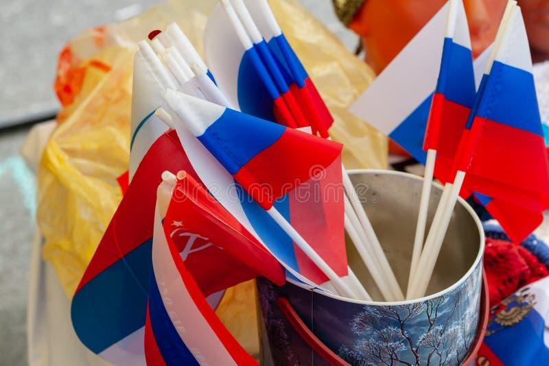 As bandeiras do russo são vendidas junto com bandeiras soviéticas O russo e os símbolos soviéticos são próximos foto de stock