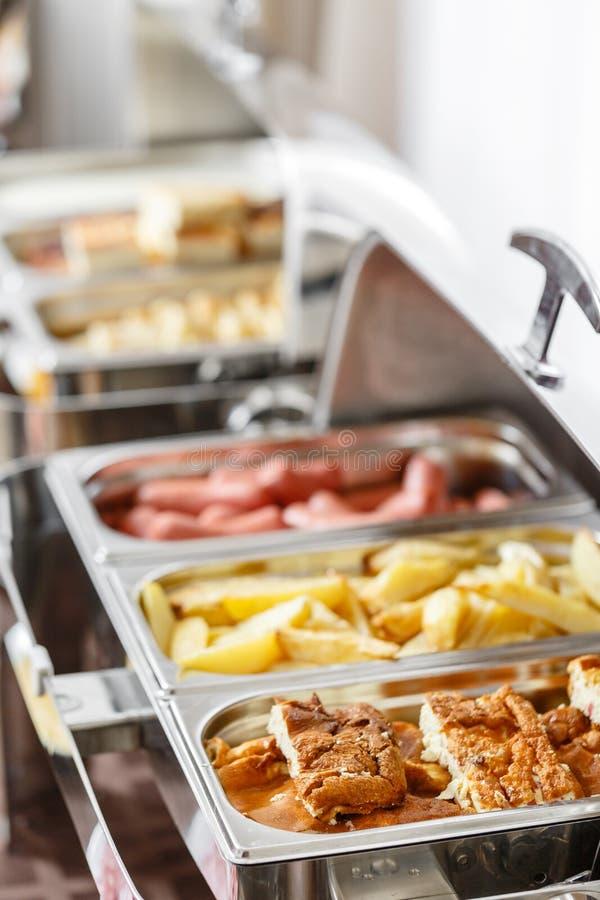 As bandejas do bufete calorosos aprontam-se para o serviço Café da manhã no smorgasbord do hotel Placas com alimento diferente fotografia de stock