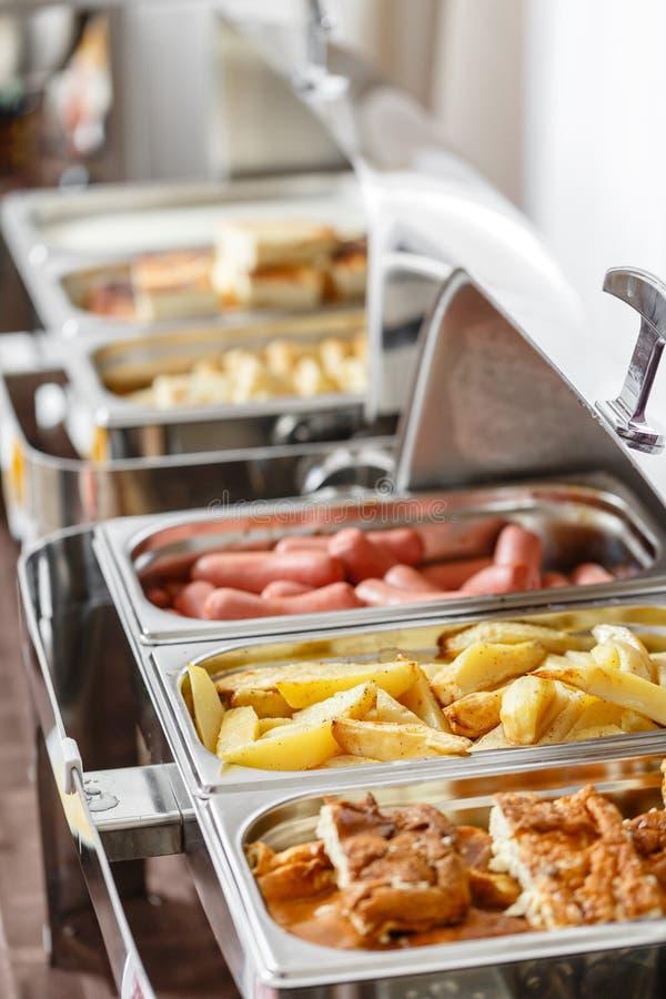 As bandejas do bufete calorosos aprontam-se para o serviço Café da manhã no smorgasbord do hotel Placas com alimento diferente imagem de stock royalty free