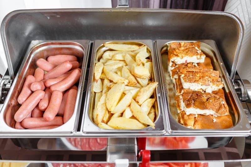 As bandejas do bufete calorosos aprontam-se para o serviço Café da manhã no smorgasbord do hotel Placas com alimento diferente fotos de stock